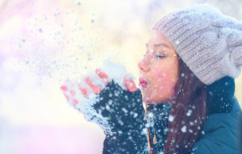 Neige de soufflement de fille d'hiver en parc givré d'hiver photos stock