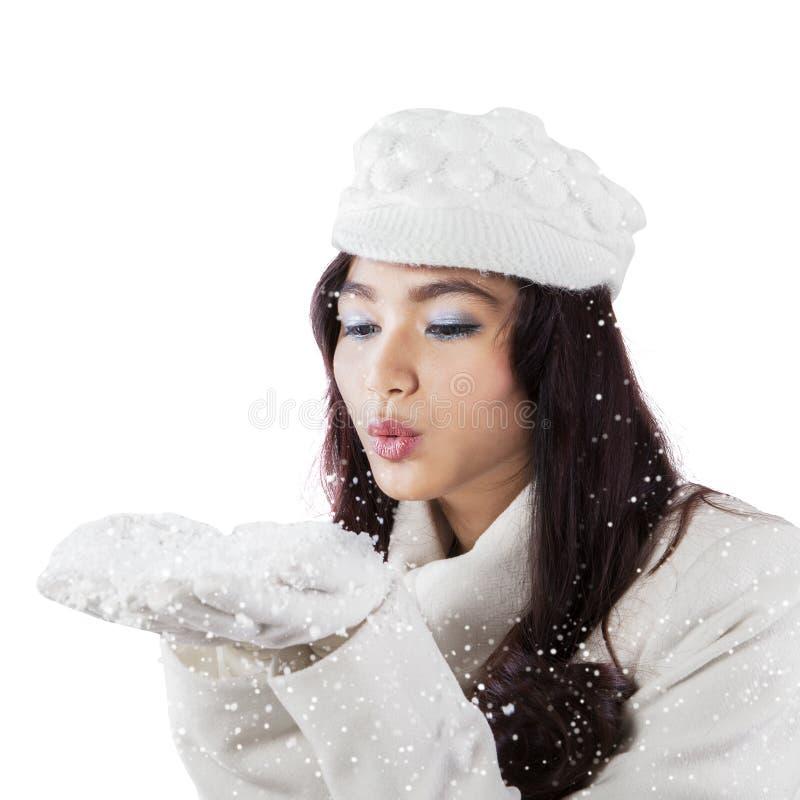 Neige de soufflement de jeune femme dans le studio image stock