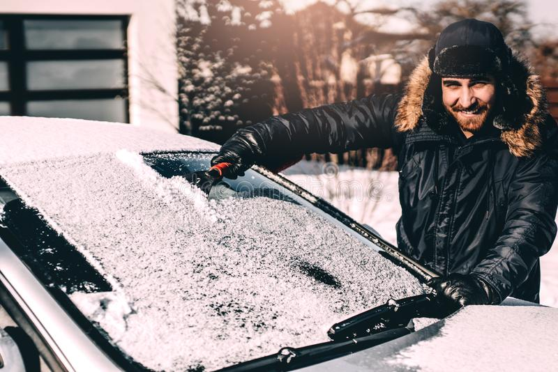 Neige de sourire et de nettoyage d'homme attirant outre de sa voiture, travaillant pendant l'hiver et l'entraînement image stock