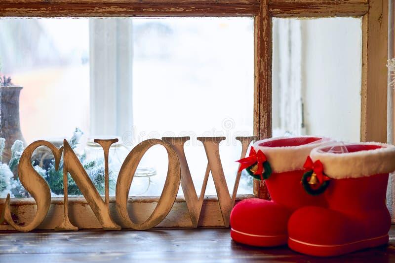 NEIGE de Word - lettres et rouge en bois avec les bottes blanches de frontière et de Noël de clochette sur le rebord de fenêtre images stock