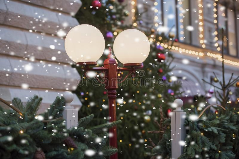 Neige en baisse de belle lanterne et un arbre de Noël photos stock