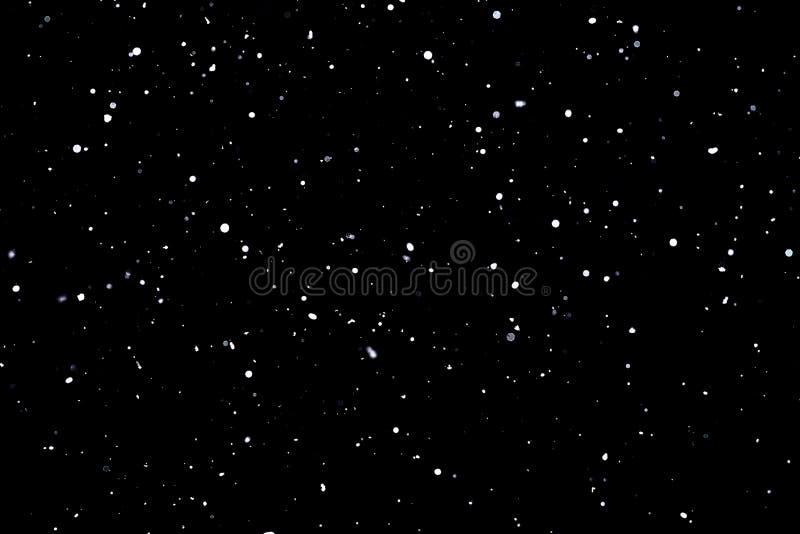 Neige en baisse sur les flocons de neige noirs de fond volant dans le ciel photographie stock