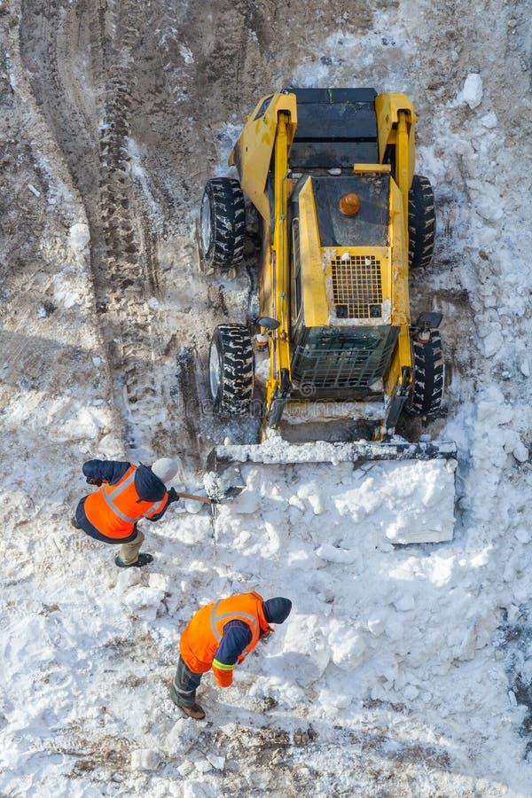 Neige-en enlevant la machine et les travailleurs nettoyez la route photographie stock libre de droits