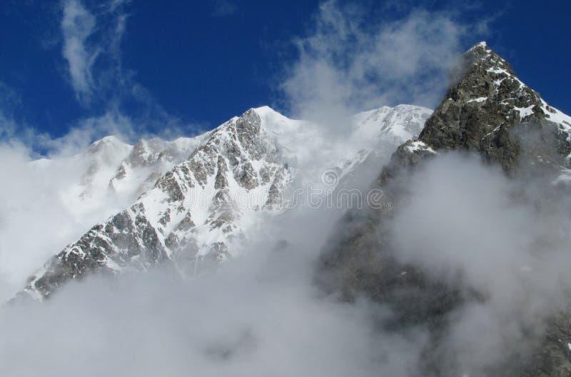 Neige et montagnes rocheuses dans le nuage photographie stock libre de droits