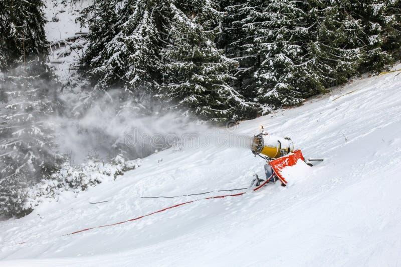Neige faisant l'arme à feu pulvérisant la poudre fraîche au-dessus de la piste de ski, arbres à l'arrière-plan photographie stock libre de droits