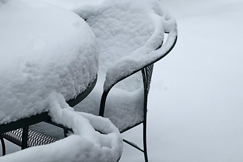 Neige fraîche sur une chaise et une table de patio en métal photos libres de droits