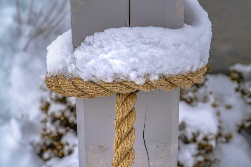 Neige glaciale sur la corde attachée à un poteau en bois images libres de droits