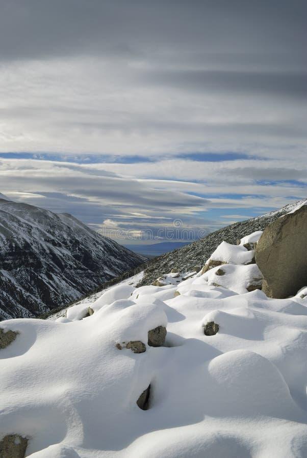 Neige intacte sur la pente de montagne au-dessus de regarder un lac bleu dans la distance images libres de droits