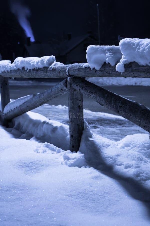 Neige tombée par hiver sur le motif en bois de barrière la nuit avec de la fumée sortant la cheminée avec la lumière arrière photo stock