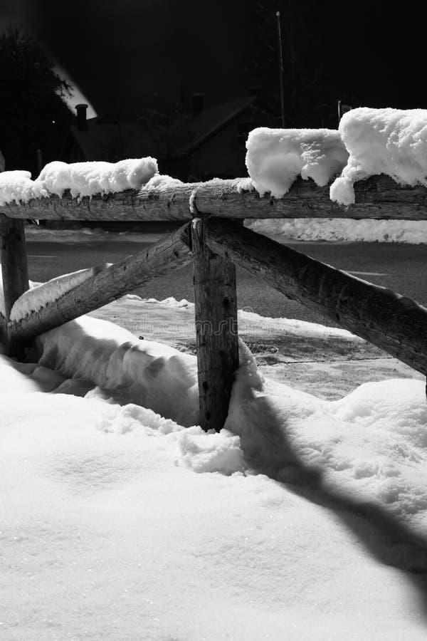 Neige tombée par hiver sur le motif en bois de barrière la nuit avec de la fumée sortant la cheminée avec la lumière arrière image libre de droits