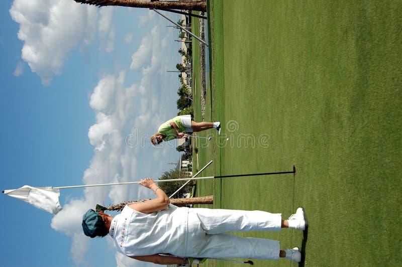 Neigen der Markierungsfahne auf Golfgrün stockfotografie