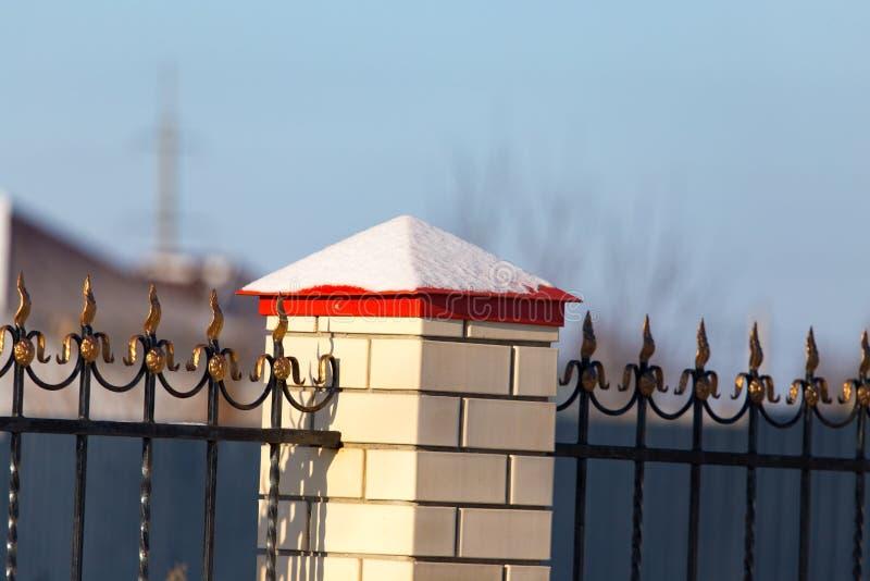Neigez sur la barrière près de la maison de cottage images libres de droits