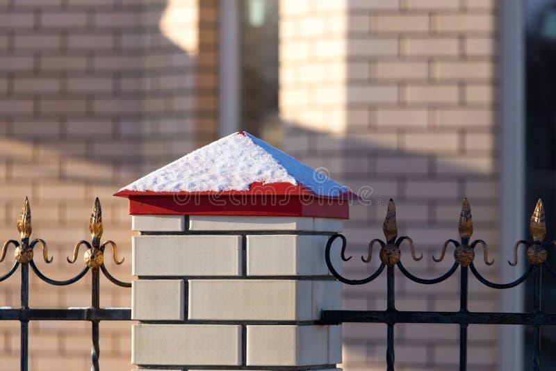 Neigez sur la barrière près de la maison de cottage photos stock