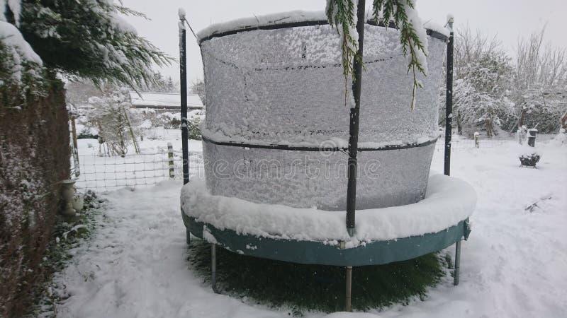 Neigez sur un trempoline dans le jardin arrière photo libre de droits
