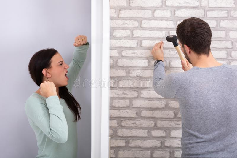 Neighbor Hitting Nail On Brick Wall With Hammer royalty free stock photography
