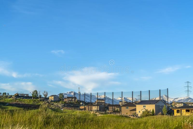 Neighborhood built on a grassy terrain with blue sky overhead on a sunny day. A snow covered mountain and electricity tower can be seen in the distance stock photo
