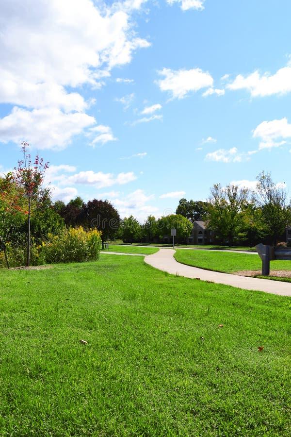 Neighborhood Sidewalk Winding Through a Park on a Beautiful, Fall Day. Neighborhood Sidewalk Winding Through a City Park on a Beautiful, Fall Day royalty free stock photos