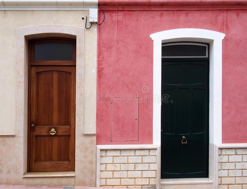 Neighboring different colored front doors next to each other in residential old houses painted in pink and white. Two neighboring different colored front doors royalty free stock photography