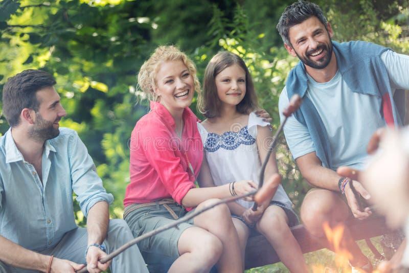 Neigung geschossen von lächelnder Familie mit männlichen Freundbratwürsten über Lagerfeuer auf Park lizenzfreies stockfoto