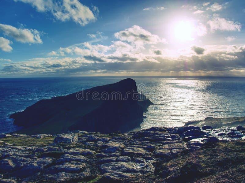 neist在岩石峭壁的点灯塔在波浪海上 蓝色晚上海和锋利的峭壁