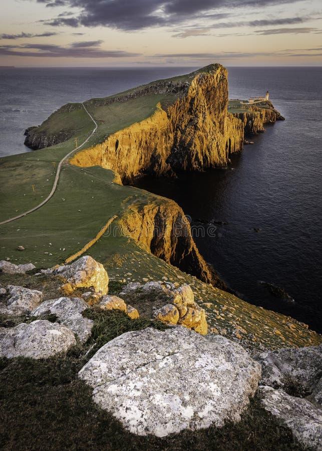 Neist punkt, berömd gränsmärke med fyren på ön av Skye, Skottland tände vid inställningssolen royaltyfri foto