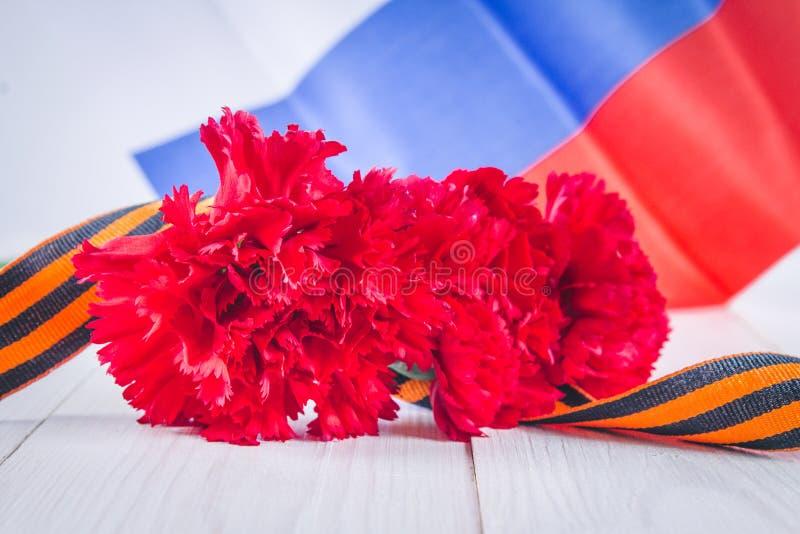Nejlika och band av St George, som ett symbol av segern mot bakgrunden av den ryska flaggan Maj 9, dagen av segern arkivfoto