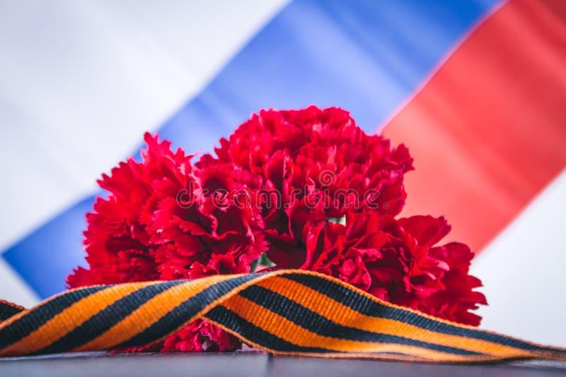 Nejlika och band av St George, som ett symbol av segern mot bakgrunden av den ryska flaggan Maj 9, dagen av segern royaltyfria foton
