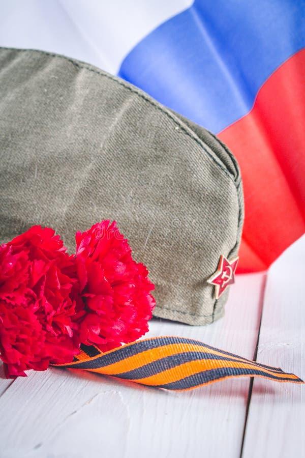 Nejlika och band av St George, som ett symbol av segern mot bakgrunden av den ryska flaggan Maj 9, dagen av segern royaltyfri foto