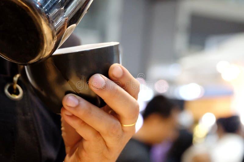 Nel fuoco selettivo della mano di Batista che fa una tazza del latte caldo fotografie stock