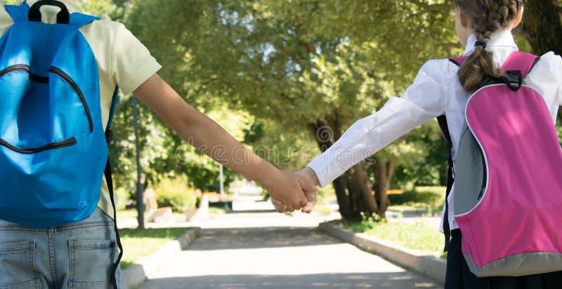 Nel parco, nell'aria fresca, primo piano, scolari che si tengono per mano, retrovisione fotografia stock libera da diritti