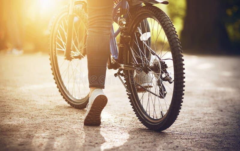 Nel parco sulla strada ? una ragazza con una bicicletta e sta andando guidare su  fotografia stock libera da diritti