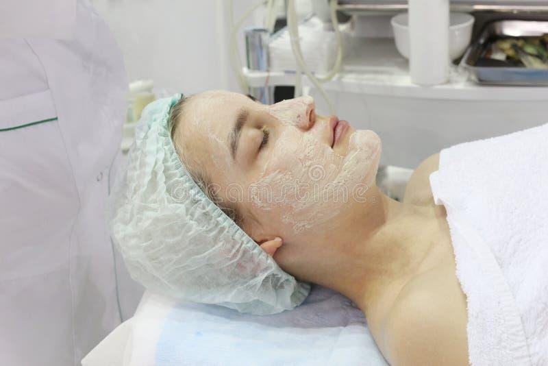 Nel salone di bellezza una giovane donna sta facendo una sbucciatura sul suo fronte immagine stock libera da diritti