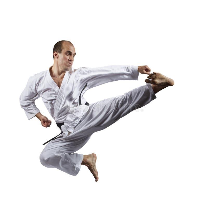 Nel salto, i battiti dell'atleta danno dei calci a su un fondo bianco isolato fotografia stock