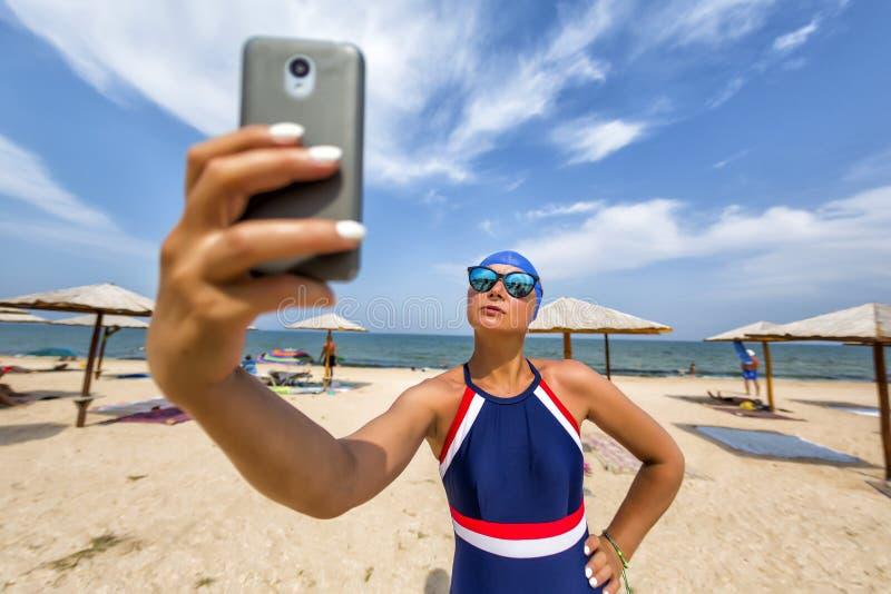 Nel sole luminoso un bello blogger della ragazza in un costume da bagno ed in un cappuccio di nuoto fa un selfie ad una stazione  fotografia stock
