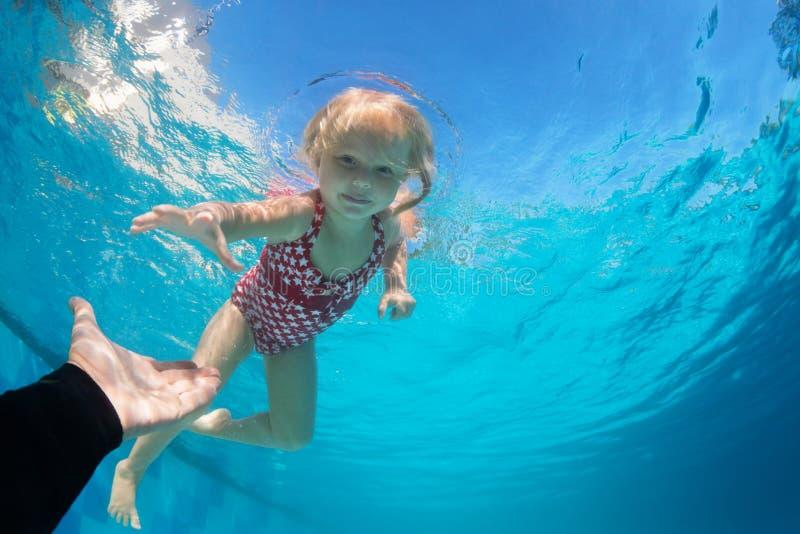 Nel tuffo del bambino della piscina subacqueo raggiungere mano estesa fotografia stock libera da diritti