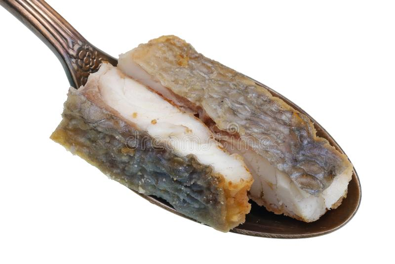 Nel vecchio cucchiaio dorato c'è un piccolo mucchio di alimento - pezzi di fritto di in raccordo dell'olio con il pesce di dorado immagini stock libere da diritti