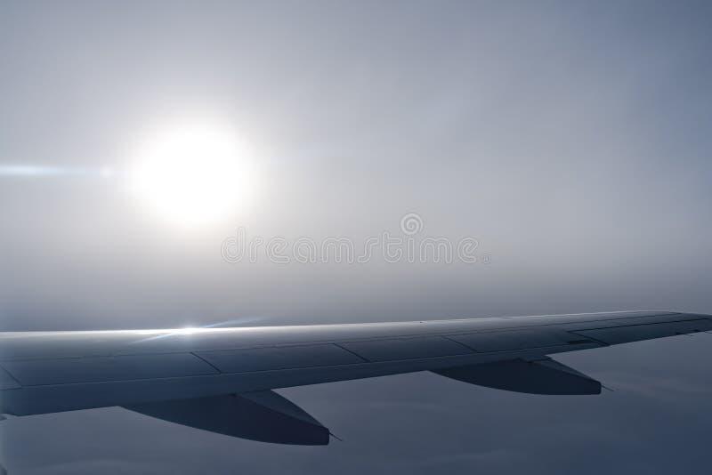 Nell'aria, vista della siluetta dell'ala di aereo con l'orizzonte blu scuro del cielo fotografie stock libere da diritti