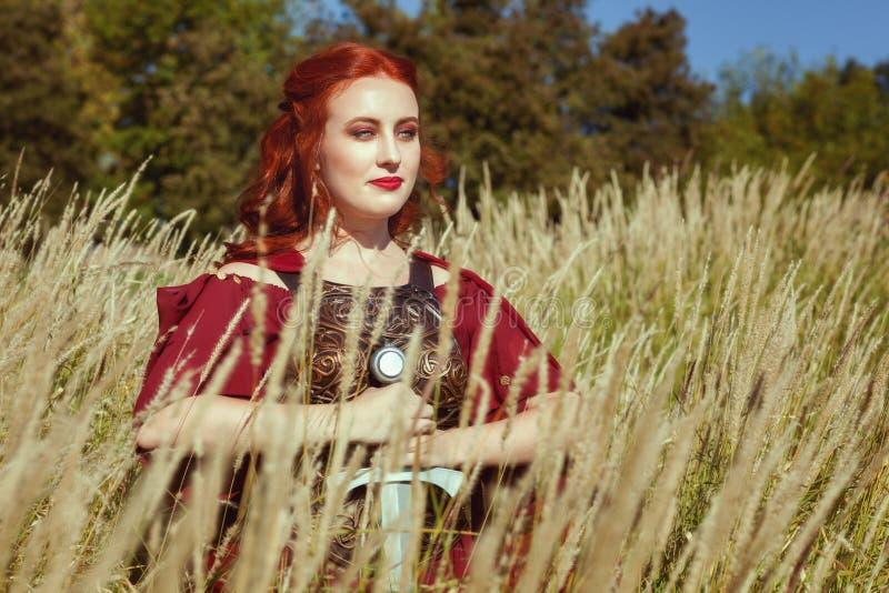 Nell'erba alta c'è una donna con una spada immagini stock
