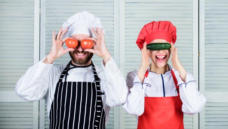 Nell'umore allegro Assistente di cuoco e del cuoco unico che gioca con le verdure in cucina Cuoco unico senior e domestica della  fotografia stock