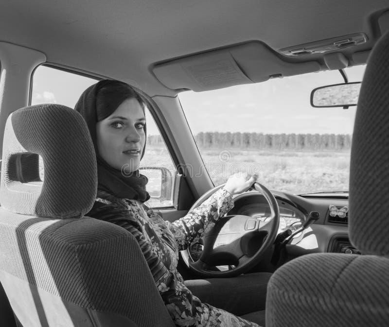 Nella bella ragazza dell'automobile in un foulard, in bianco e nero fotografia stock libera da diritti