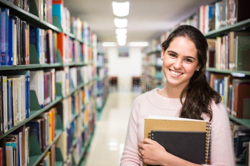 Nella biblioteca - studentessa graziosa con i libri che lavorano in una h fotografia stock