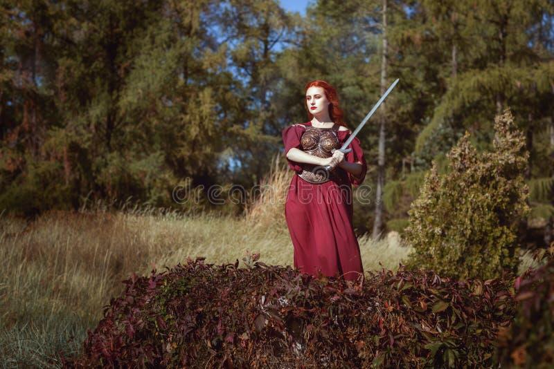 Nella foresta, una donna con una spada fotografia stock