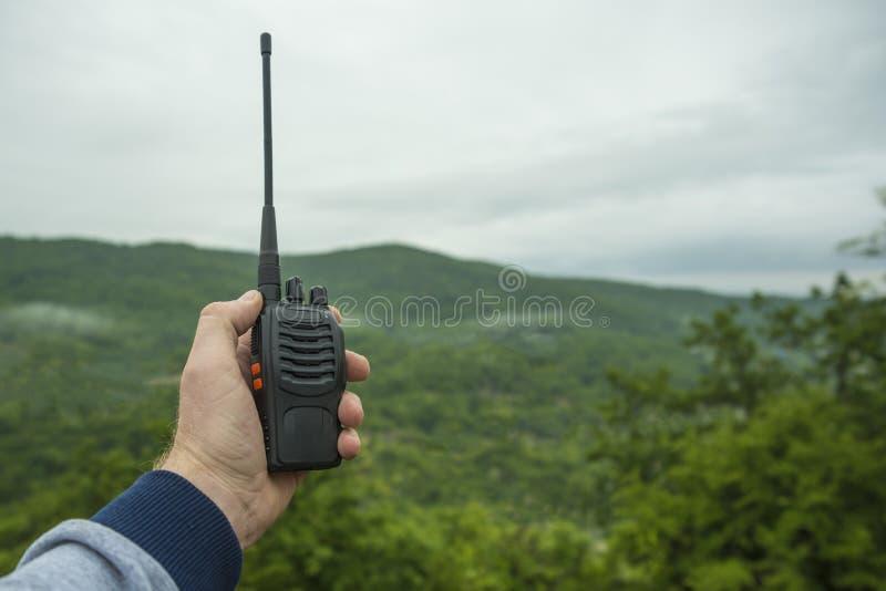 Nella mano di un walkie-talkie dell'uomo per all'aperto immagine stock libera da diritti