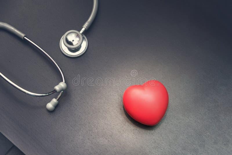 nella vista superiore, cuore rosso con l'attrezzatura medica dallo stetoscopio sui precedenti dello scrittorio di medico Concetto fotografia stock libera da diritti