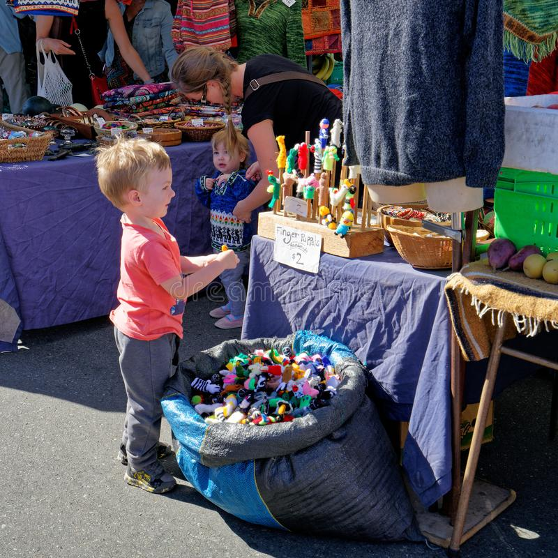 Small boy enthralled by the finger puppets on a Nelson market stall. Nelson, Nelson/New Zealand - February 2, 2019: Small boy enthralled by the finger puppets on royalty free stock images