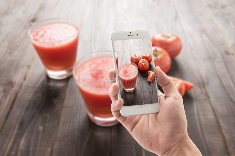Nemend foto van plantaardige die smoothie van rode rijpe tomaten wordt gemaakt stock afbeeldingen