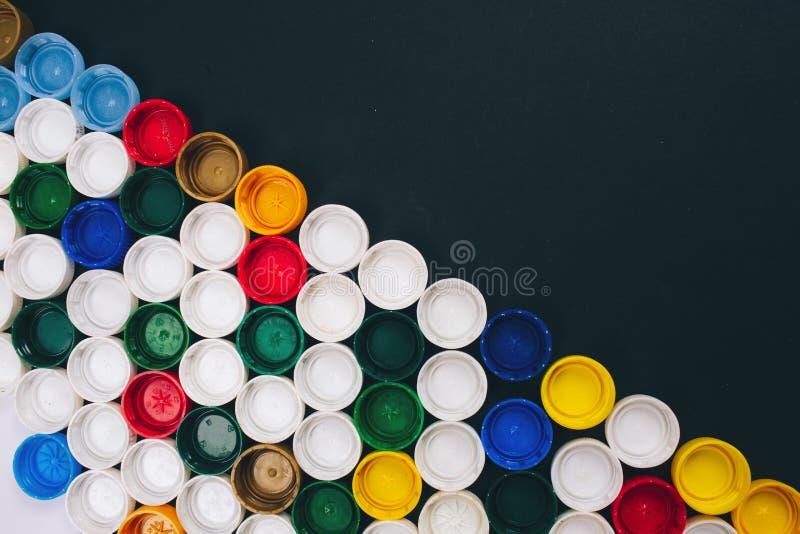 Nenhum conceito pl?stico Conceito do problema da polui??o Fundo colorido das tampas plásticas diferentes encontradas diagonalment foto de stock