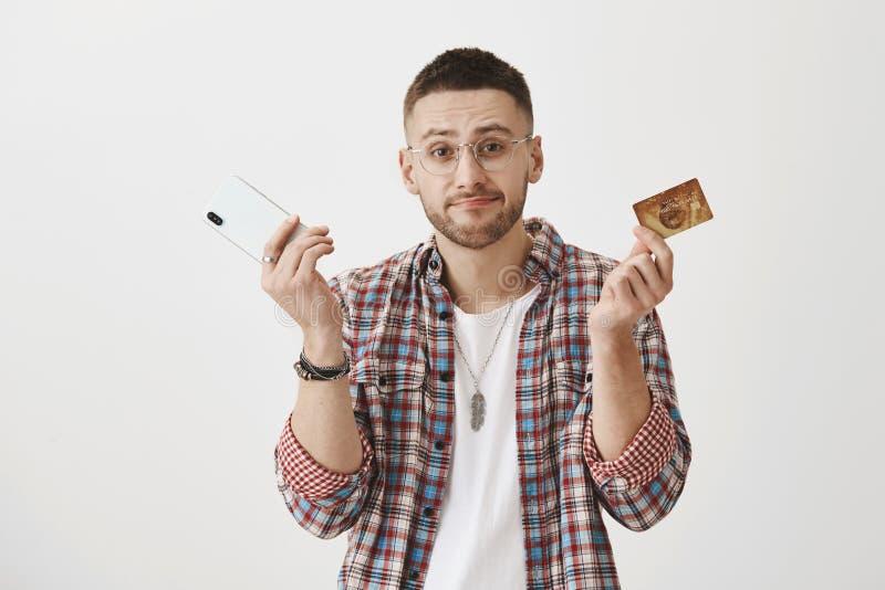 Nenhum dinheiro nenhum smartphone Retrato das sobrancelhas consideráveis desagradadas sombrios do empregado, shrugging e levantar imagens de stock