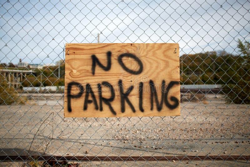 Nenhum estacionamento exprime escrito à mão em uma placa em uma cerca imagem de stock
