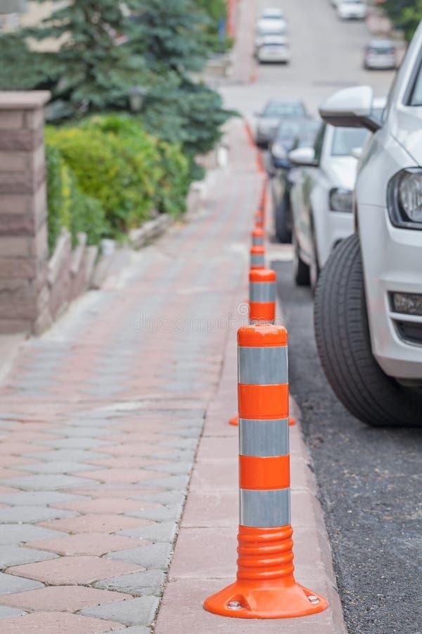 Nenhum estacionamento no pavimento Fila do poste de amarração no pavimento ao lado dos carros imagens de stock royalty free